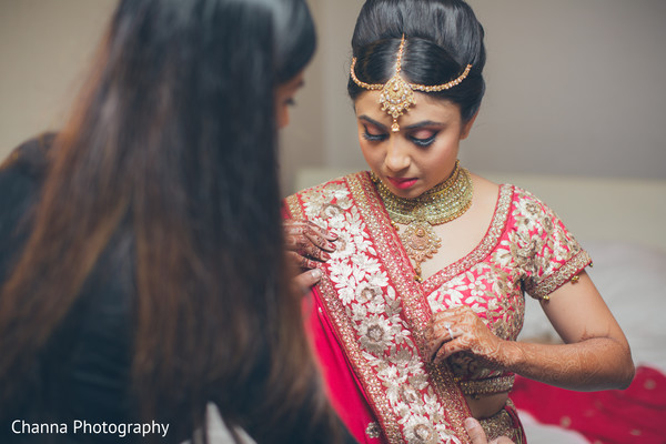 Indian bride adjusting the final details of her attire.