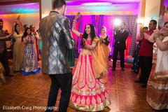 Happy couple dancing at their sangeet celebration.