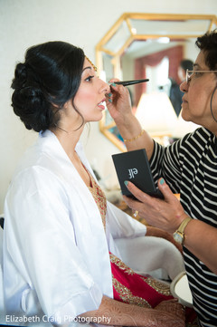 Indian bride gets her make up done.