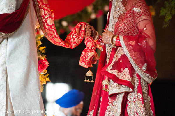 Sikh bride follows the groom holding on to her end of the palaa.