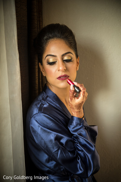 Fabulous indian bride finishing her look with some red lipstick.