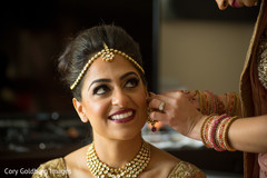 Indian bride putting  her  earrings on.