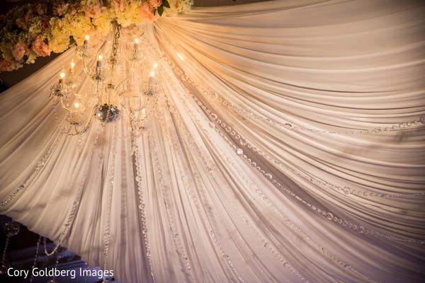 Elegant draped white mandap and crystal chandelier.