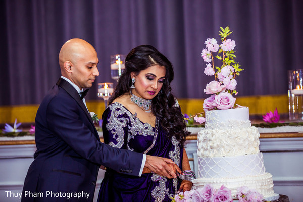 Indian couple cutting their cake at wedding reception