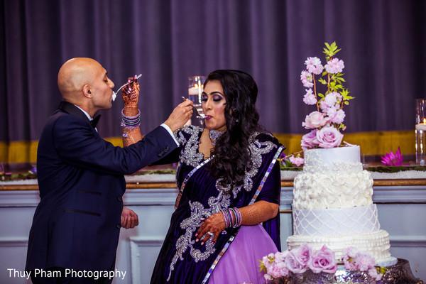Indian couple eating cake at wedding reception