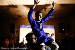 Indian groom carried by guests at the sangeet.