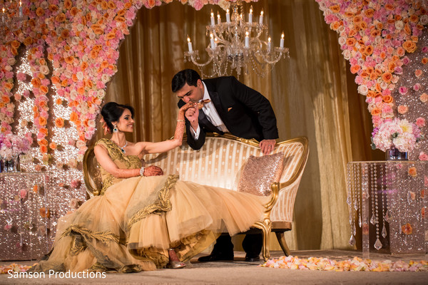 Indian groom kissing bride's hand at wedding reception