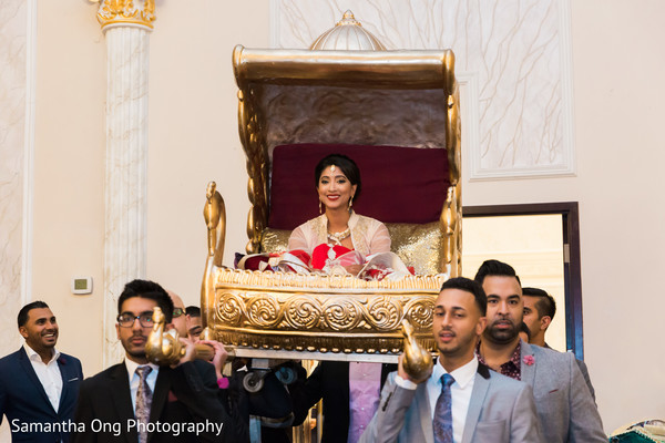 Beautiful indian bride enters the ceremony carried in a golden palanquin.