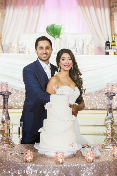 Indian Couple Posing Next To Their Wedding Cake Photo 92080