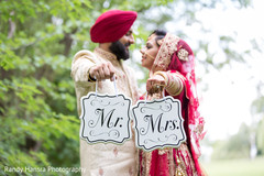 Lovely indian couple holding Mr. and Mrs. signs.