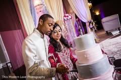 Indian couple cutting their wedding cake