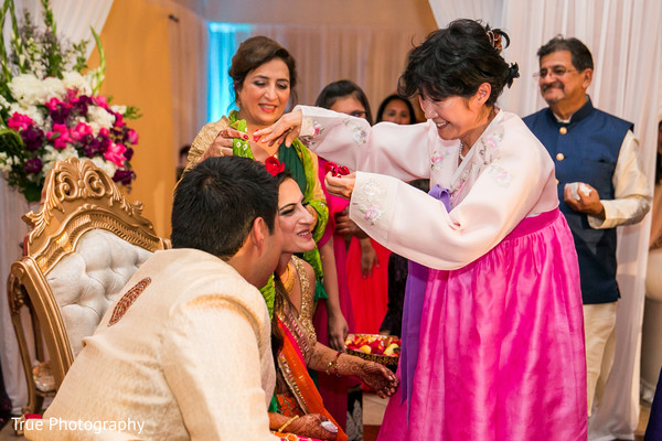 Indian couple being blessed by the groom's mother.