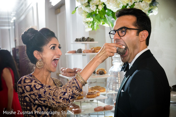 Groom trying the delicious desserts in Washington, D.C. Indian Fusion Wedding by Moshe Zusman Photography Studio