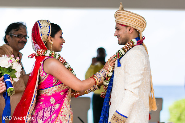 Couple also exchange garlands during the ceremony. in Nieuwpoort, Curaçao Indian Wedding by KSD Weddings