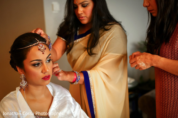 Indian bride getting some help with her jewelry. in Cancun, Mexico Indian Wedding by Jonathan Cossu Photographer
